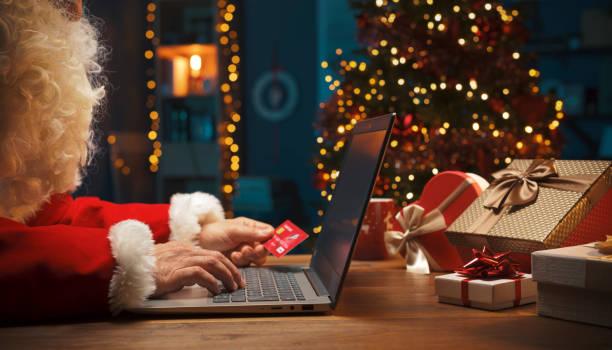 Santa doing online shopping at Christmas stock photo