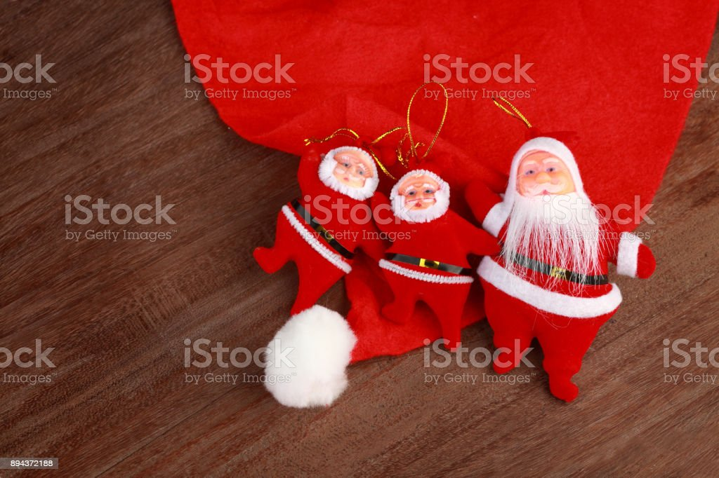 Santa dolls and cap on a wooden background stock photo