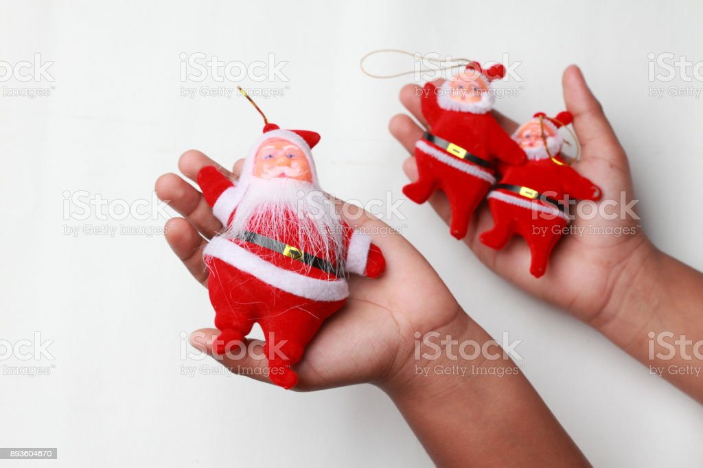Santa dolls on a Child's hand against white background stock photo
