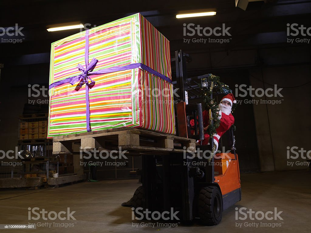 Santa driving forklift carrying big present in warehouse 免版稅 stock photo