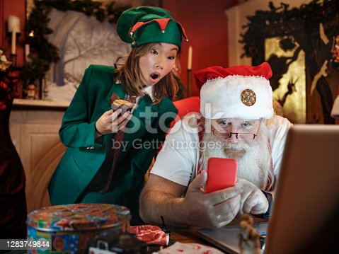 Santa Claus using a computer in his house to do a Christmas video conference. He is typing his present list on the red mobile phone. At some point  Elf joins him to see what is going on.