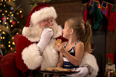 istock Santa Enjoying Cookies and Milk with a Child 505561871