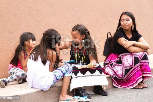 Santa Fe, NM, USA - August 20, 2016: A Native American family sits near an adobe wall at the 2016 Santa Fe Indian Market. One of the girls wears a traditional native dress. The market, now in its 95th year, is spread out all around the historic Santa Fe Plaza, showcasing North American Indigenous arts and culture. About 1,000 artists from 220 tribes participate in the two-day event.