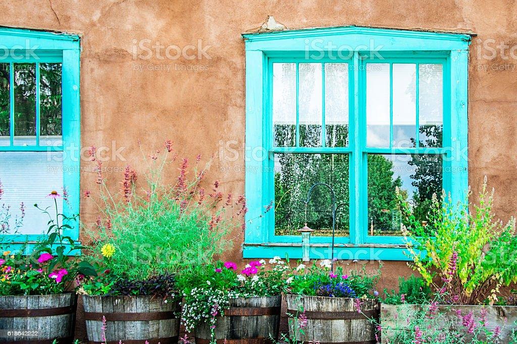 Santa Fe Blue Windows on Stucco Wall with Flowers stock photo