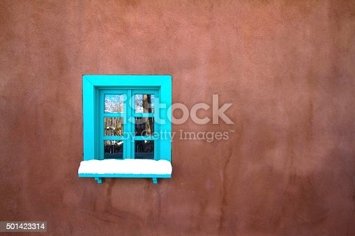 Santa Fe in snow: a small blue window in a large brown adobe wall. Blue trim is a traditional architectural feature of Santa Fe, NM. Copy space available.