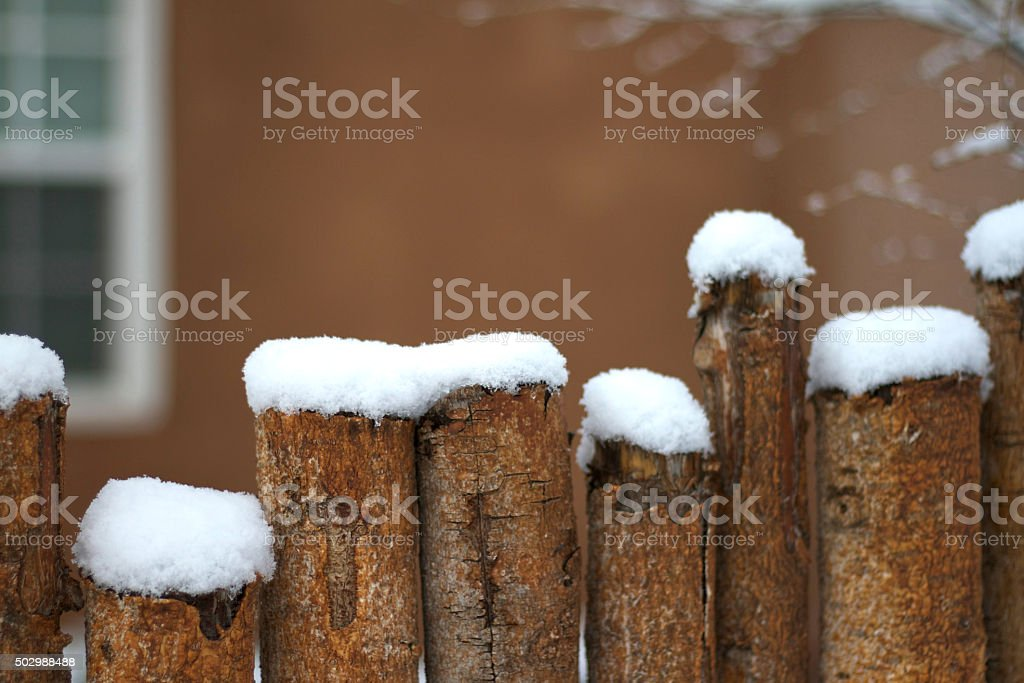 Santa Fe in Snow: Rustic Coyote Fence, Adobe House stock photo