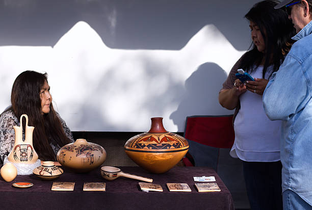 2016 santa fe indian market: hopi potter with art work - hopi stock photos and pictures