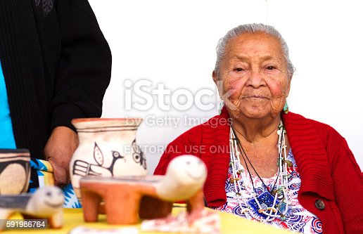 Santa Fe, NM, USA - August 20, 2016: Traditional potter Crucita Melchor from Santo Domingo Pueblo with her work at the 2016 Santa Fe Indian Market. She was the winner of the Lifetime Achievement Award at the 2013 Indian Market. The market, now in its 95th year, is spread out all around the historic Santa Fe Plaza, showcasing North American Indigenous arts and culture. About 1,000 artists from 220 tribes participate in the two-day event; visitors number about 175,000.