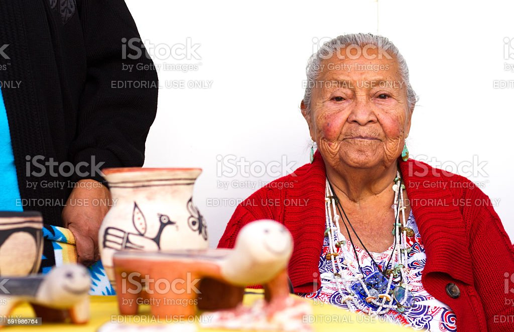 2016 Santa Fe Indian Market: Kewa Pueblo Potter with Work stock photo