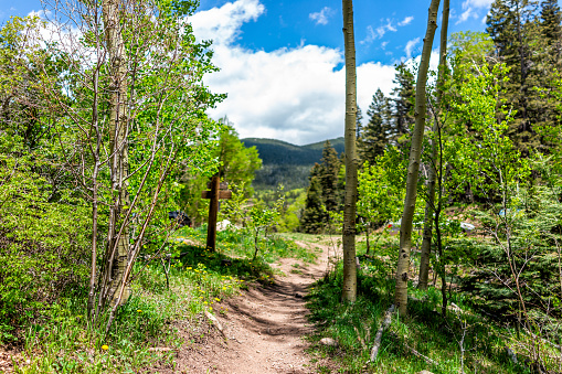 Santa Fe National Forest park trail with sign entrance at trailhead Sangre de Cristo mountains and green aspen trees by parking lot