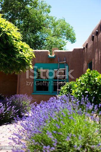 Santa Fe, NM: A traditional old adobe house with sunny interior bricked courtyard with a catalpa tree, bushes, and lavender in summer.