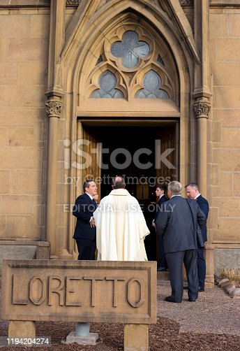 Santa Fe, NM: A clergyman talking to a group of people outside the Loretto Chapel in downtown Santa Fe at dusk.
