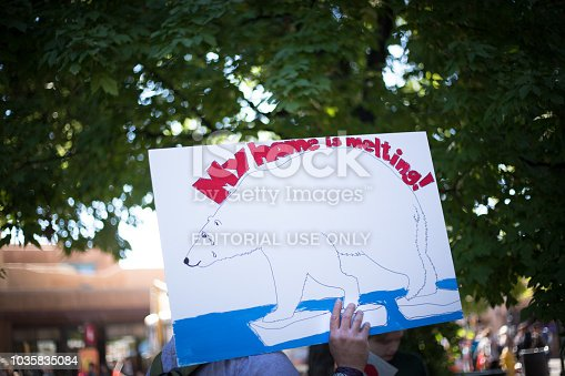 Santa Fe, NM: Someone holds a climate change warning sign at the Santa Fe Fiesta, a 10-day event that takes place at the end of each summer.