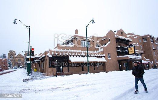 Santa Fe, NM: A lone man walking on a snowy Old Santa Fe Trail near the historic La Fonda Hotel in downtown Santa Fe.