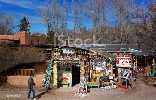 Santa Fe, NM: A man walking past an art gallery on Canyon Road, a famous road full of shops and art galleries.