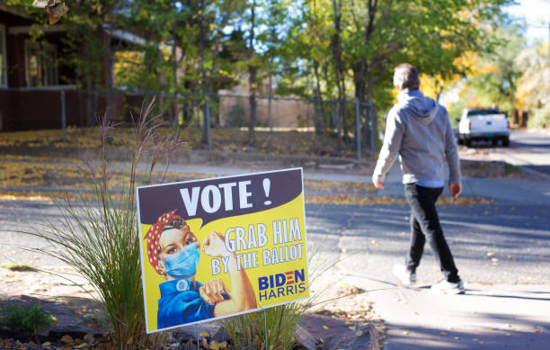 "Santa Fe, NM: Man Walking Past VOTE! Sign Santa Fe, NM: A man walking past a sign in downtown Santa Fe reading ""VOTE! Grab Him By the Ballot Biden Harris"" featuring Rosie the Riveter. joe biden stock pictures, royalty-free photos & images"