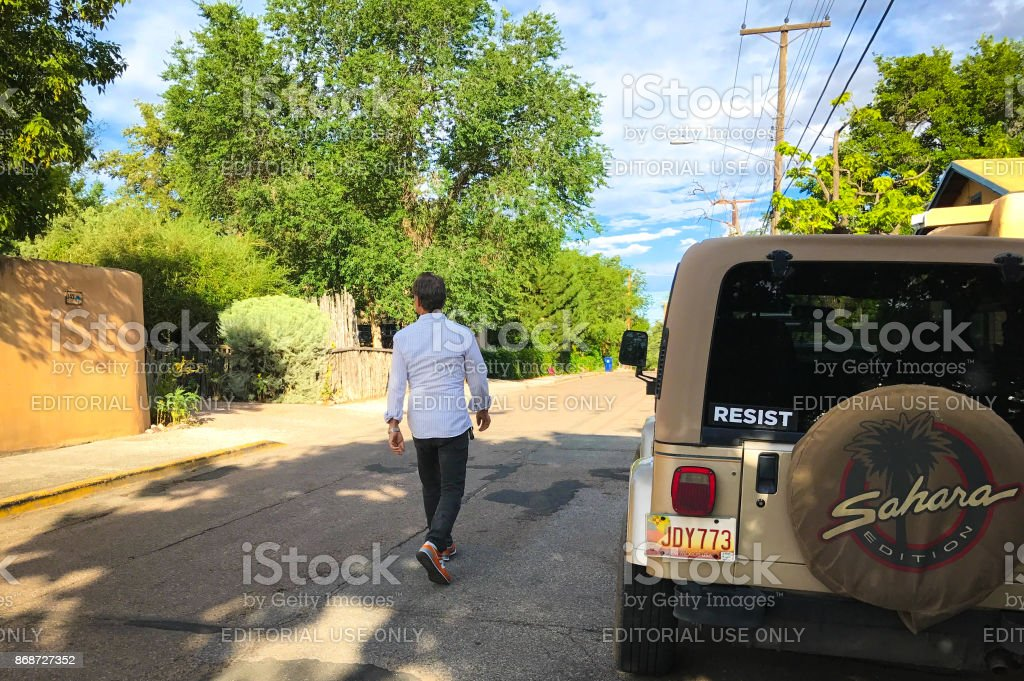Santa Fe, NM: Man Walks Past Car with 'RESIST' Sticker stock photo