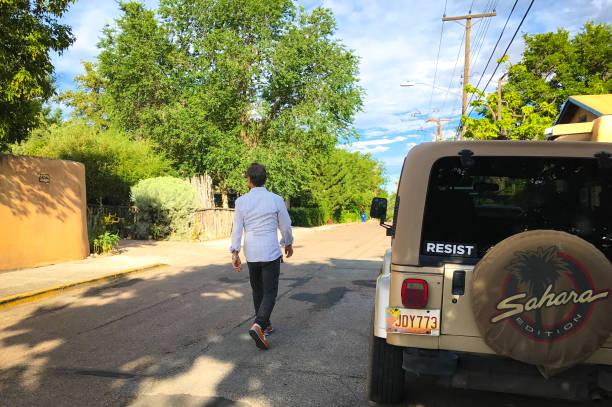 Santa Fe, NM: Man Walks Past Car with