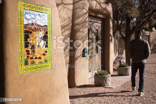 Santa Fe, NM: A man walk past a Mexican-made tile mosaic with a Spanish theme on Canyon Road, a famous road full of adobe structure and art galleries.