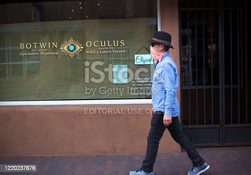 Santa Fe, NM: A  an with a bandana mask walks by a closed shop in downtown Santa Fe, NM during the COVID-19 pandemic.