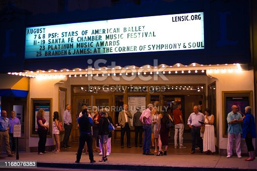 Santa Fe, NM: Nighttime crowd of theater-goers outside the historic Lensic Theater in downtown Santa Fe during intermission.