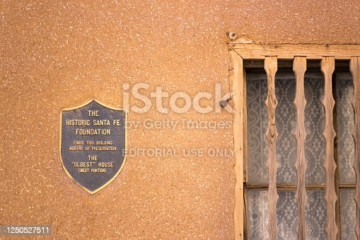 """Santa Fe, NM: Santa Fe's """"Oldest House"""" landmark just off the Old Santa Fe Trail in downtown Santa Fe, NM. Close-up shot of the bronze memorial plaque on an adobe wall."""