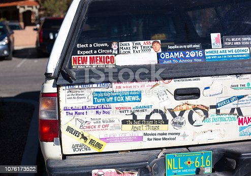 Santa Fe, NM: A pickup truck covered with bumper stickers, including political ones concerning Obama, Trump, Mitt Romney, Fox News.