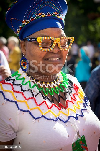 Santa Fe, NM: A South African artist in elegant beaded clothing and sunglasses at the Folk Art parade on the historic Santa Fe Plaza. The free parade kicks off the annual International Folk Art Market (IFAM), where artists from over 100 countries participate.