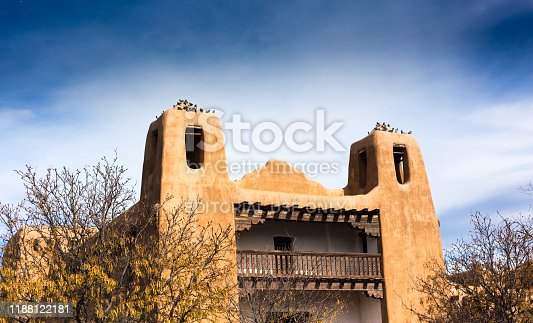Santa Fe, NM:  St Francis Auditorium with flocks of pigeons on the two bell towers. This community auditorium, constructed in traditional adobe style, is located just a block from the historic downtown Plaza.