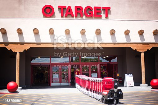 Santa Fe, NM:  A Target employee pulls red shopping carts into the Santa Fe NM store. Santa Fe's Target is constructed in the Southwest Pueblo architectural style.