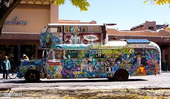 Santa Fe, NM: A vintage hippie bus parked on the Santa Fe Plaza, with typical adobe architecture in the background.