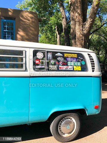 """Santa Fe, NM: A vintage VW van window covered with bumper stickers, including peace symbols, a """"Hippie Power"""" sticker, and a sticker reading """"Make Art Not War."""""""