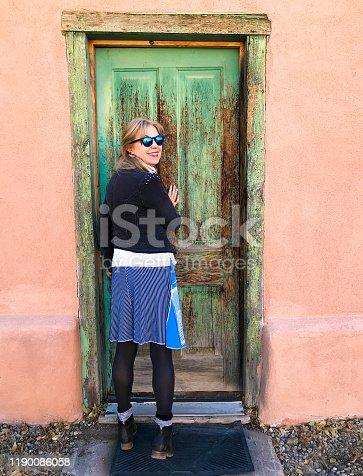 Santa Fe, NM: Woman at green door, adobe wall. Shot on Canyon Road.