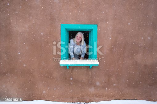 Santa Fe, NM: A blond senior woman at the turquoise window of an old adobe house in a snowstorm. Copy space available. House built in the 1800s.