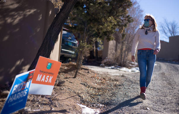 Santa Fe, NM: Woman Walking Near Mask and Election Sign Santa Fe, NM: A woman walking near a sign thanking people for wearing a mask and a political sign for Biden/Harris. joe biden stock pictures, royalty-free photos & images
