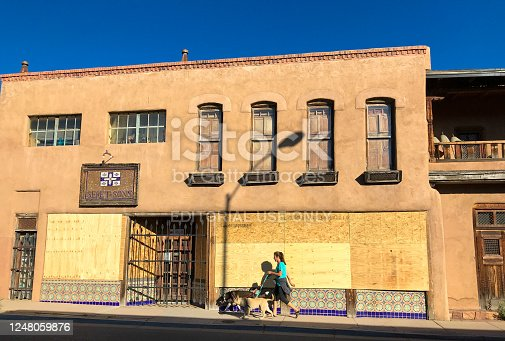 Santa Fe, NM: A woman walks her dog in morning sunlight near a boarded-up shop in downtown Santa Fe during the June 2020 Black Lives Matter protests.