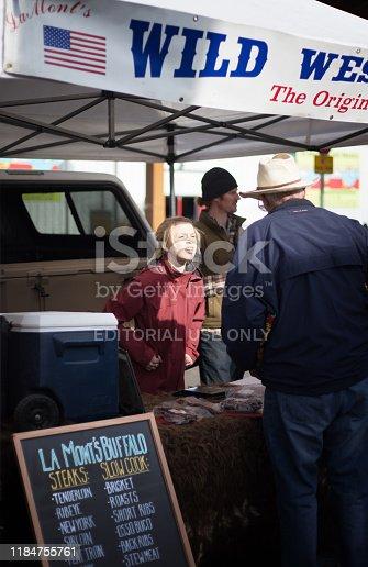 Santa Fe, NM: A young female vendor selling buffalo meat to a customer in a straw cowboy hat at Santa Fe's Saturday Farmer's Market.