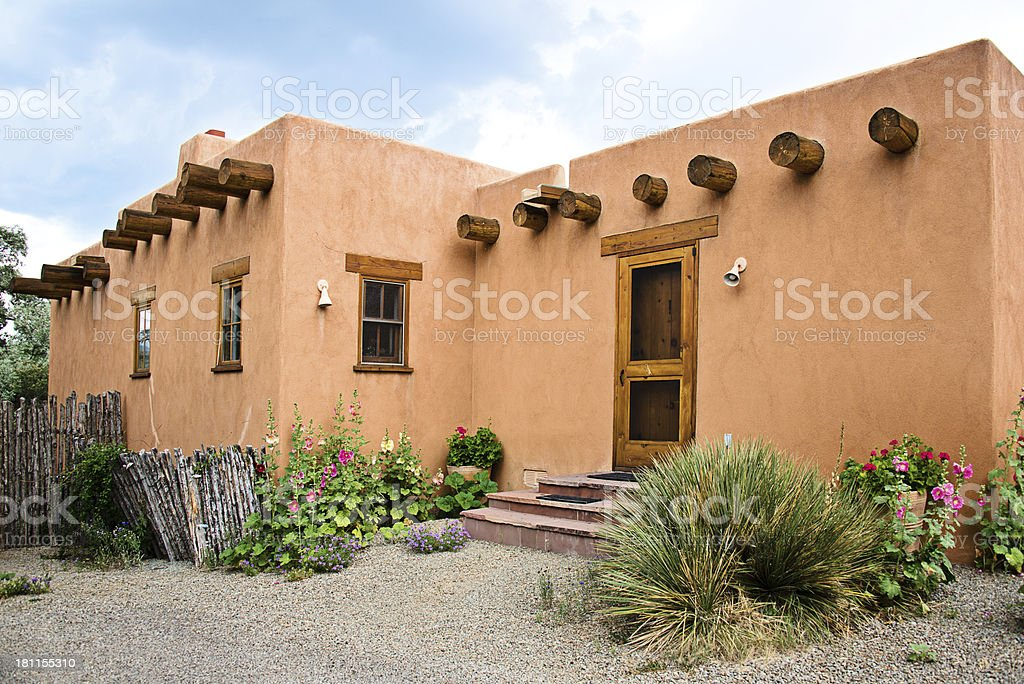 Santa fe old adobe house with stucco wall and flowers for Adobe house construction cost