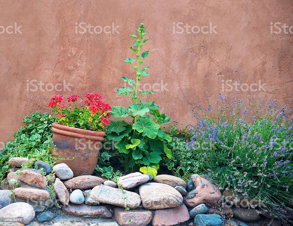 Santa Fe Stucco Wall and Hollyhock Flowers stock photo