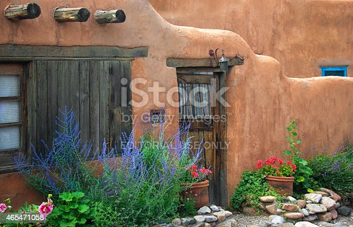 Santa Fe, USA - July 20, 2014: Old Adobe House with brown stucco wall and flowers on Canyon Road, Santa Fe. Canyon Road is a half-milestreet in the Historic District of Santa Fe. Santa Fe is the oldest capital city in the United States and the oldest city in New Mexico.