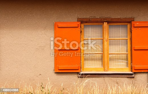 Santa Fe Style: An adobe wall (not plastered so the straw content is plainly visible) with a yellow window frame and bright orange shutters. Pale prairie grass in the foreground. Copy space on the wall.