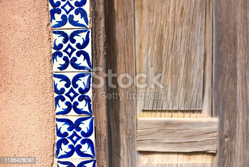 Santa Fe Style: Antique blue and white Mexican  Talavera tiles between wood door and adobe wall. Close-up shot.