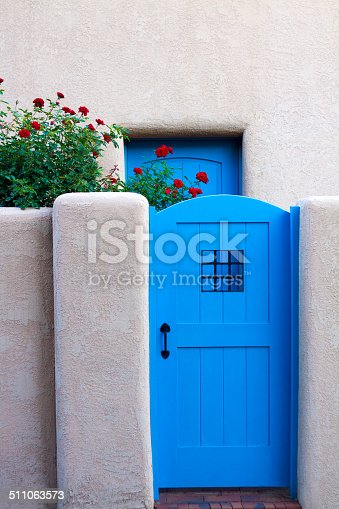 Santa Fe style: a blue door, red roses, and adobe walls. Shot in Santa Fe, NM. Some copy space on top.