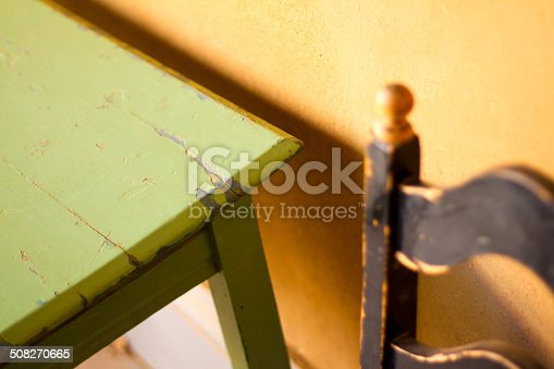 Detail from a rustic kitchen: a chipped green table, old black chair, and a rough yellow adobe wall. Shot in Santa Fe, New Mexico.