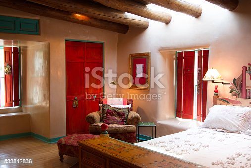Santa Fe style: colorful rustic-chic bedroom with viga beams, thick adobe walls that are hand-troweled with a