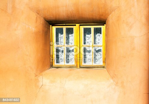Santa Fe Style: Cute little yellow window with a white lace curtain in a sunlit adobe wall