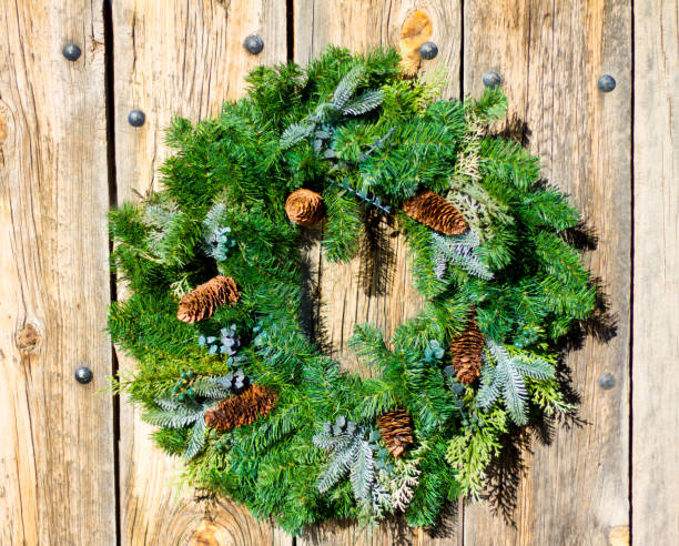 santa fe style: green christmas wreath on rustic door - evergreen plant stock photos and pictures