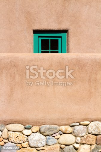 Santa Fe style: a small green window in an adobe house behind an adobe wall. Copy space available.