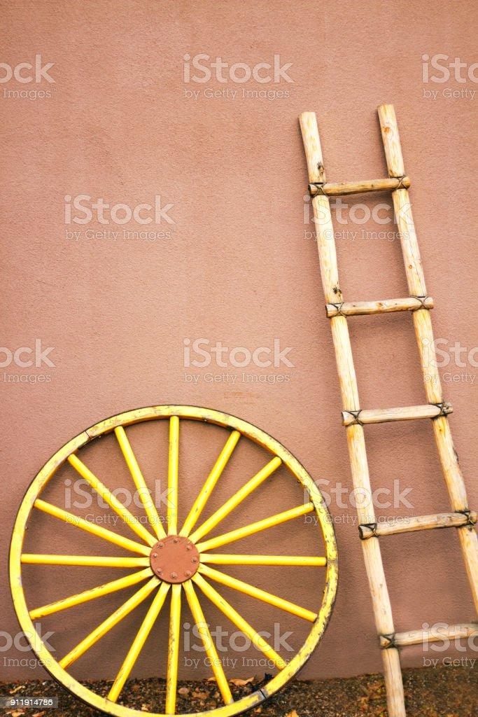 Santa Fe Style: Kiva Ladder, Wagon Wheel, Adobe Wall stock photo