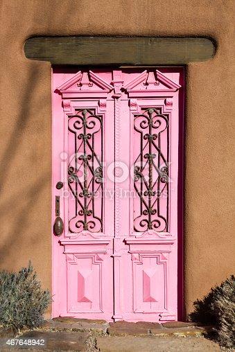 Santa Fe style: an antique pink door in an adobe wall. Shot in Santa Fe, NM.